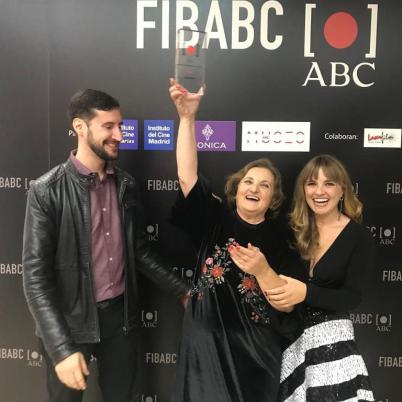 Margarita Asquerino levantando su galardón junto a Paula Pielfort y Carlos Blanco-Barberà